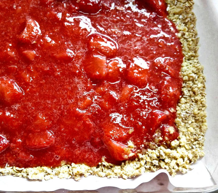 Add strawberry filling on the crumble base