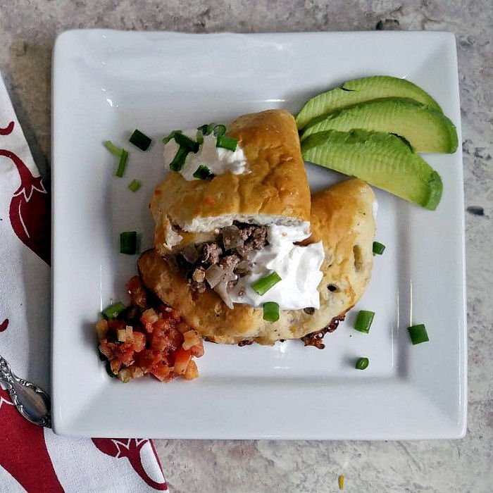 Plate of taco melts with avocados, salsa and sour cream.