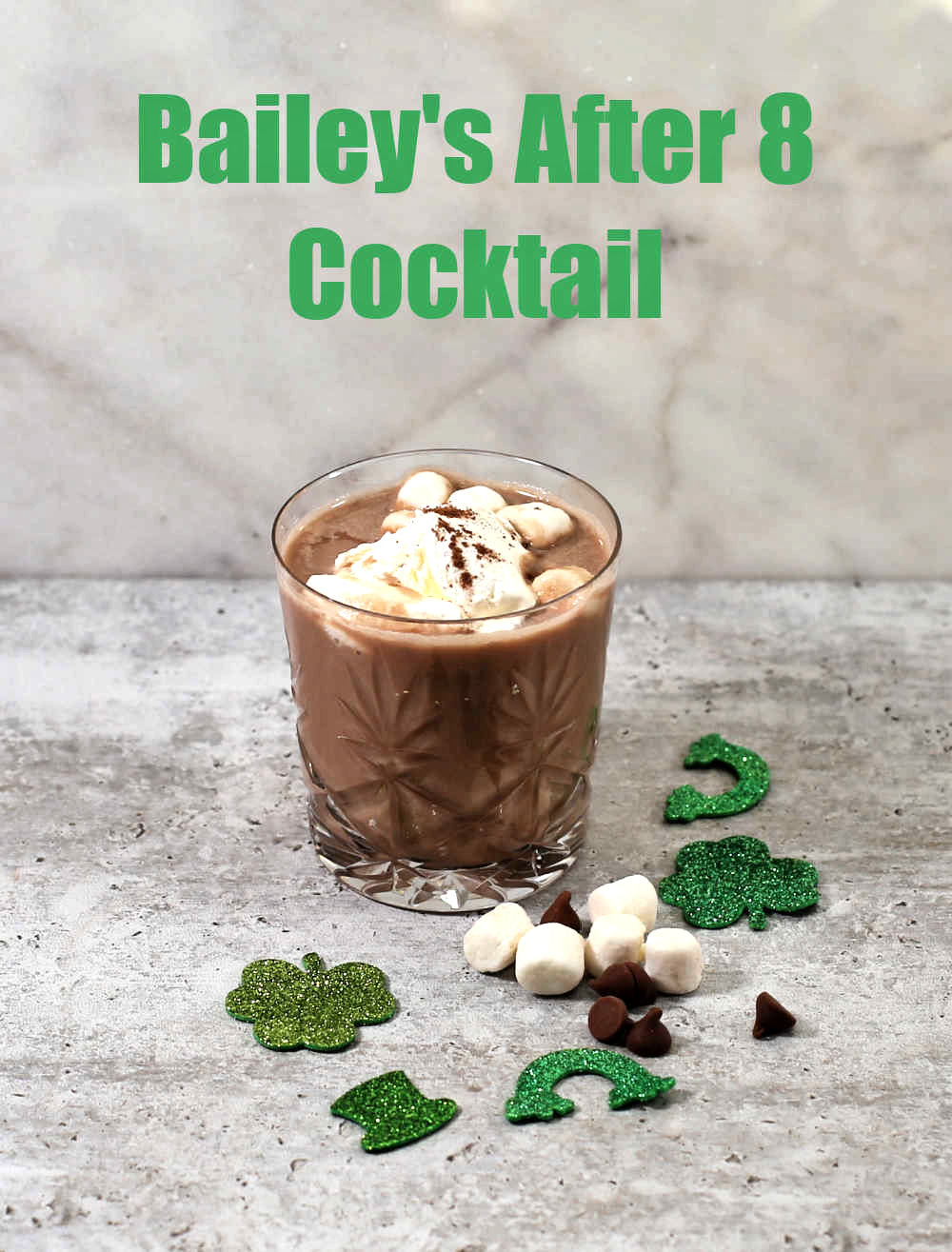 Chocolate drink with whipped cream and marshmallows near green shamrocks and rainbows with words reading Bailey's After 8 Cocktail.