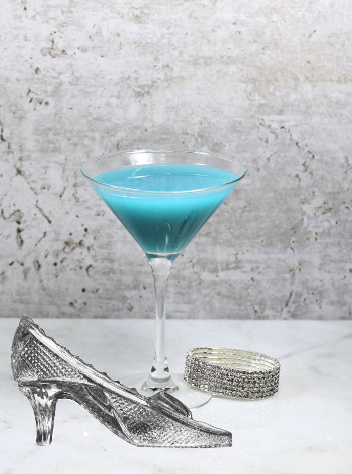 Blue cocktail in a martini glass with a rhinestone bracelet and glass slipper.