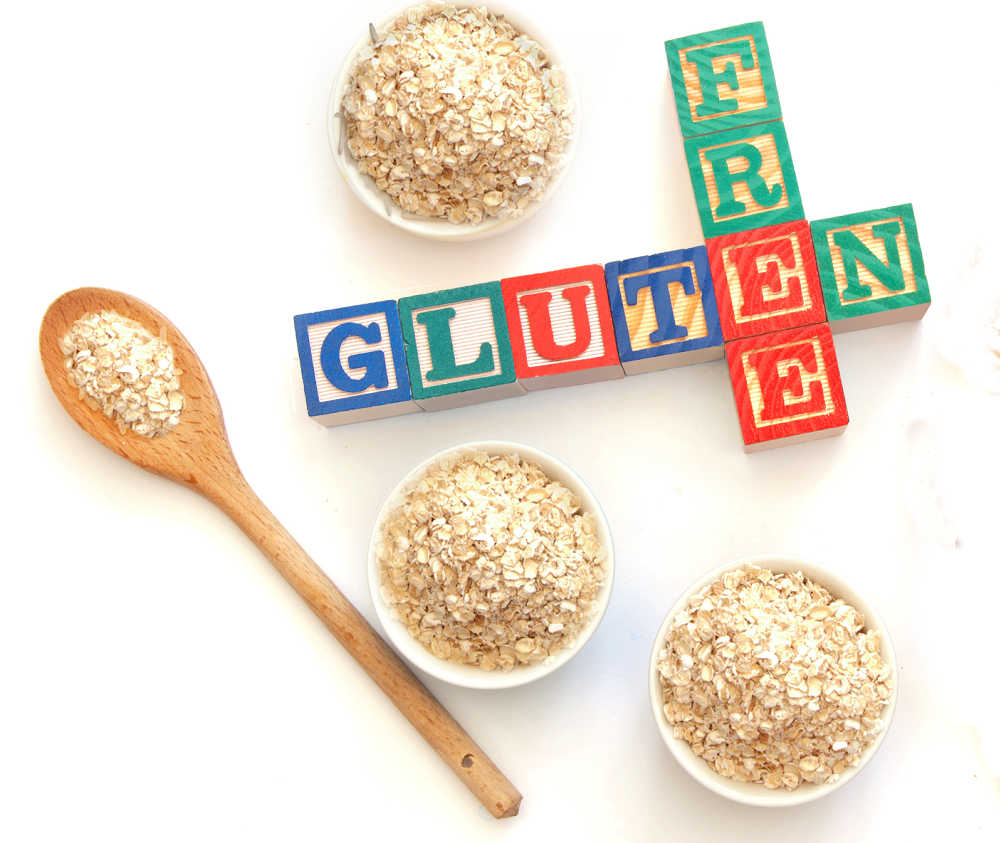 Rolled oats in bowls and on wooden spoon with blocks reading gluten free