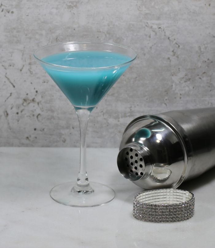 Cinderella cocktail near a cocktail shaker with rhinestone bracelet.