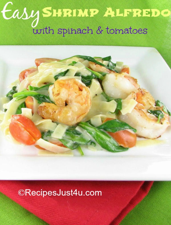 shrimp, tomatoes and spinach on white plate with a red napkin and words reading Easy Shrimp Alfredo with Spinach and Tomatoes.