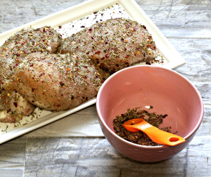 seasoning chicken breasts with a special spice rub
