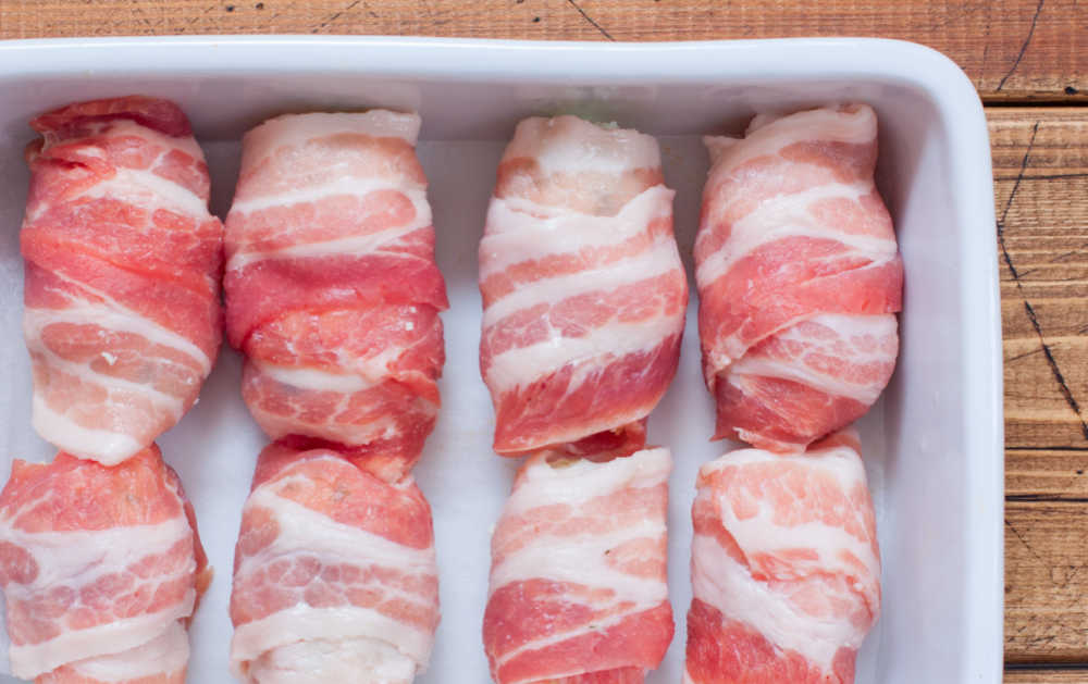 Bacon wrapped chicken breasts in a white baking pan.