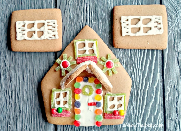 decorate gingerbread house pieces with royal icing and candy