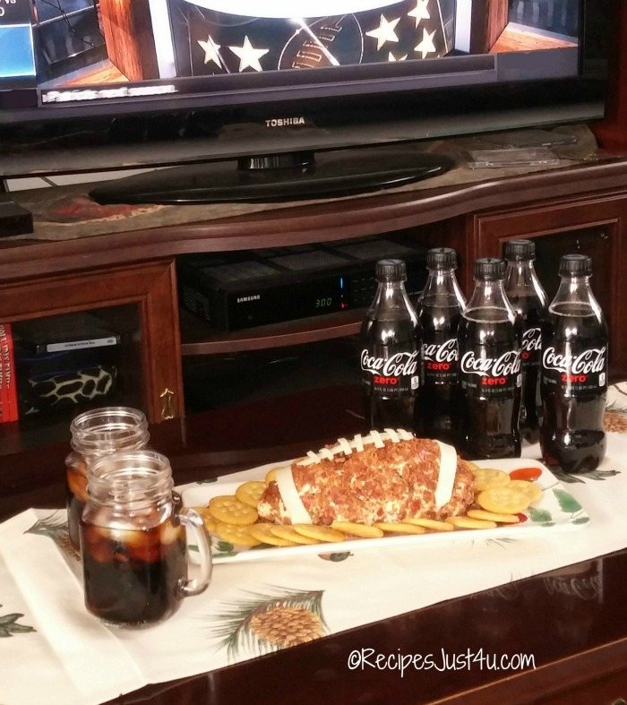 Coffee table display of football cheese ball and coke zero in front of a TV