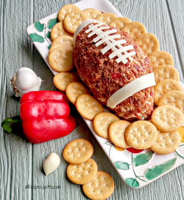Spicy football cheese ball on a platter with crackers, garlic and red pepper.