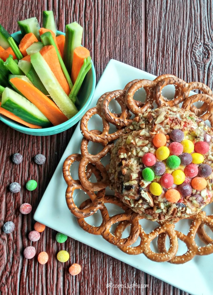 This Skittles Sour cheese ball is served with knot pretzels and vegetable sticks and topped with sour Skittles candy.