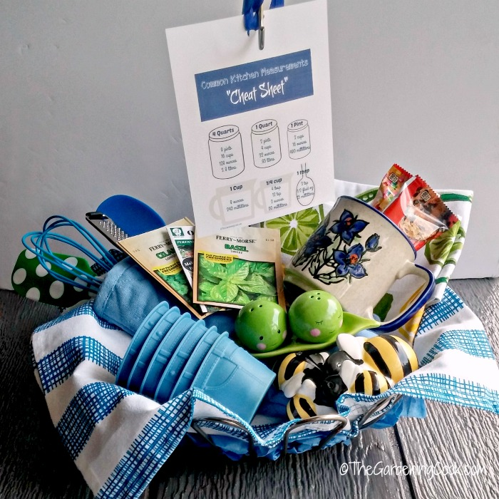 Kitchen Gift basket with blue towel, mug, salt, seeds, whisk, and pepper shakers and silicone muffin cups.