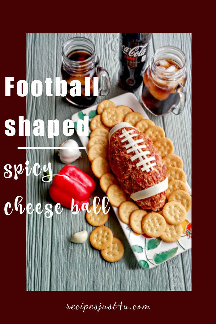 Cheese ball and crackers on a plate with words reading Football shaped cheese ball.