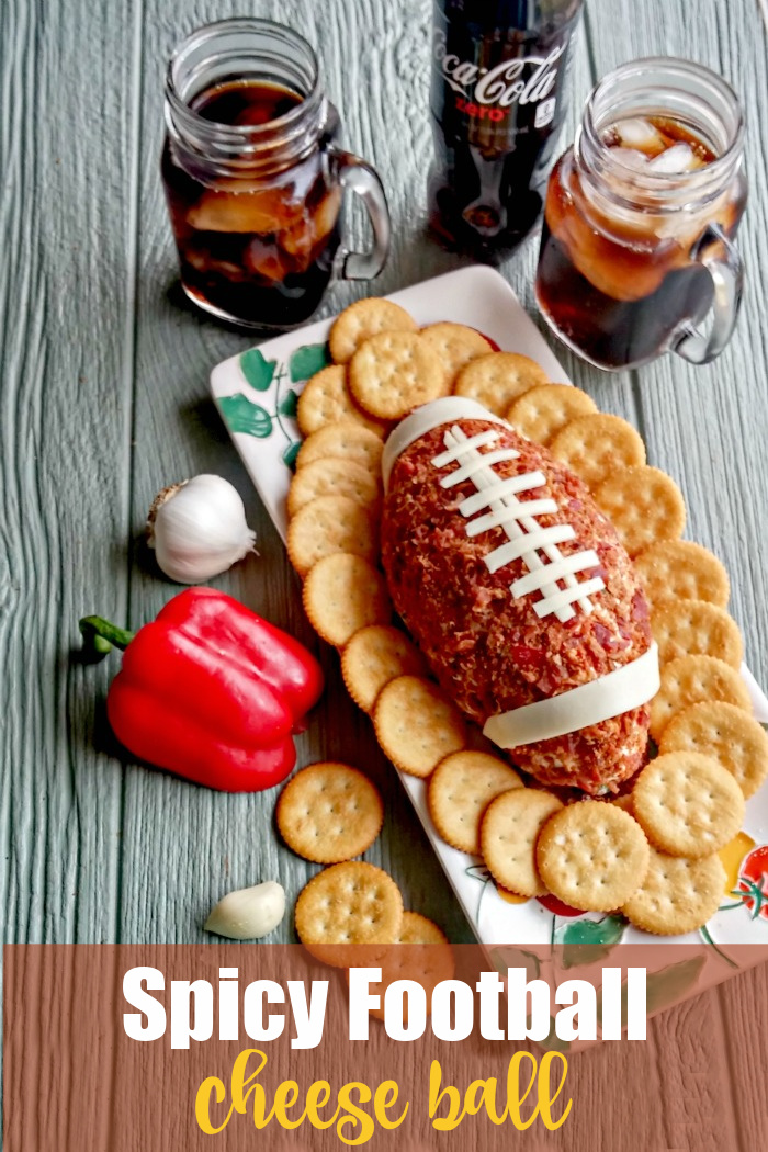 Cheese ball in the shape of a football with drinks, crackers and red pepper and text reading Spicy Football Cheese Ball.