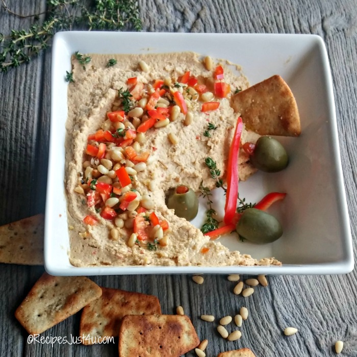 Bowl of red pepper and pine nut hummus with pita chips and olives.
