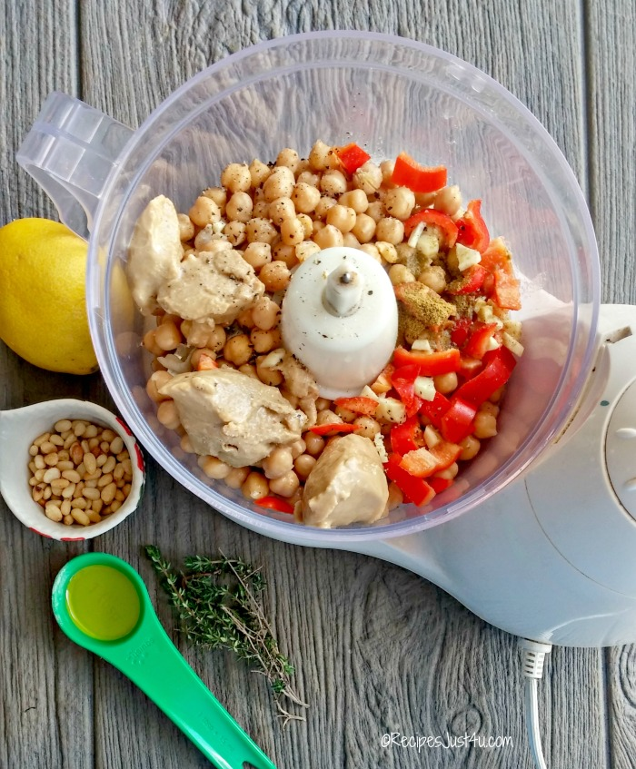 Pine nuts, roasted red peppers and Tahini in a food processor near a lemon, some pine nuts, thyme and olive oil.