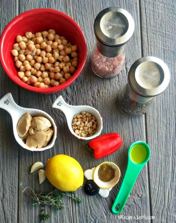 Pine nuts, sea salt, pepper, garlic, tahini, red pepper, lemon, thyme and olive oil on a grey board.