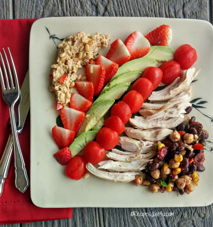 Avocado, strawberries, chickpea salad and sliced chicken with red pepper and pine nut hummus on a plate with a red napking and knife and fork.