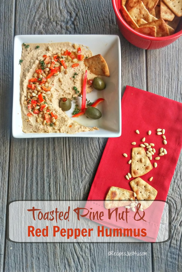 Hummus in a bowl with pinenuts and olives near a red napking with pita bread and words reading Toasted Pine Nut and Red Pepper Hummus.