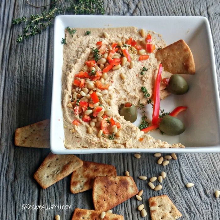 Red pepper and pine nut hummus in a bowl with pita bread and olives.