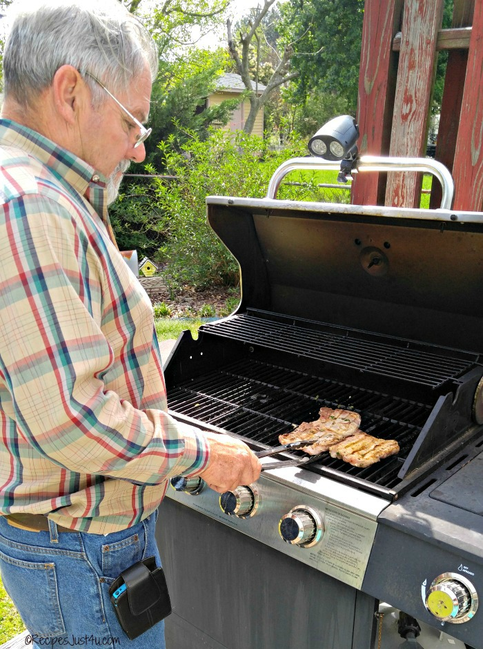 Man grilling pork chops on an outdoor grill.