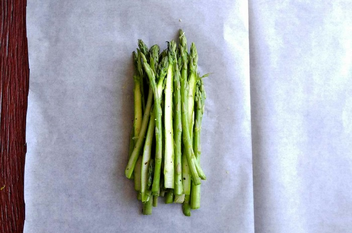 Place a layer of asparagus on the parchment paper