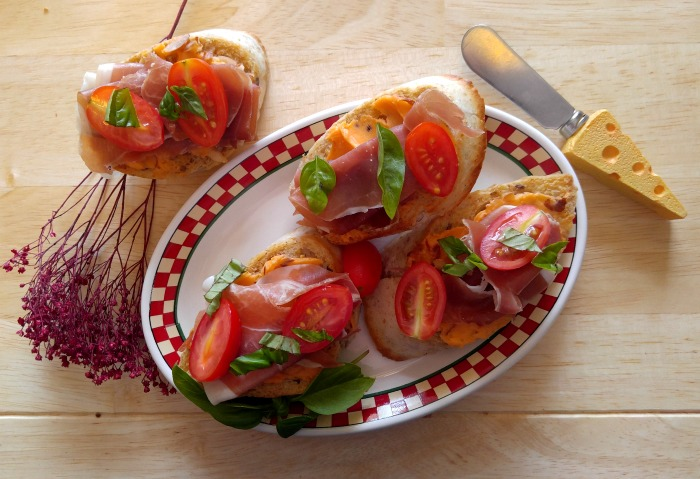 This prosciutto and tomato crostini appetizer uses basil for flavoring.
