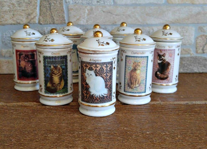 Cats of Distinction spice jars on a wooden board.