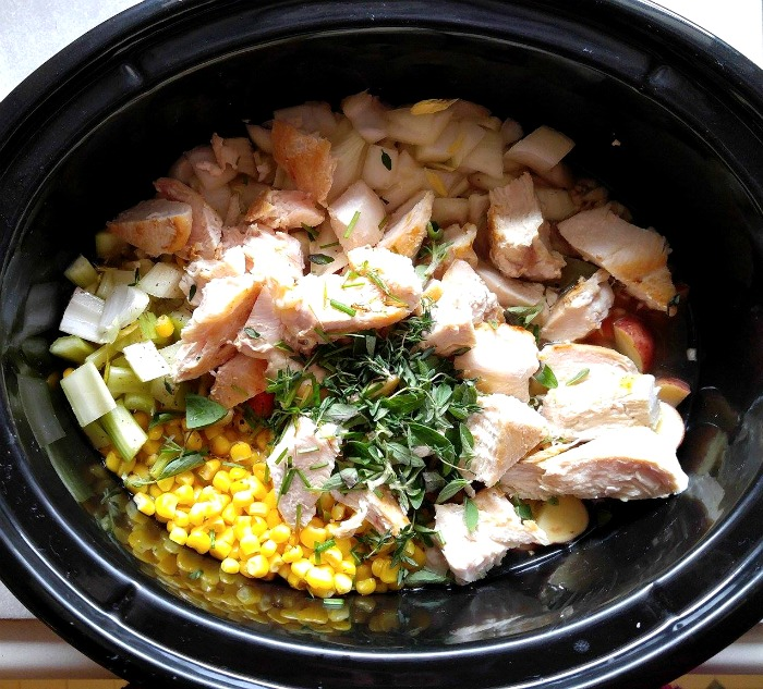 Add chicken stock and chicken along with fresh herbs to the crock pot.