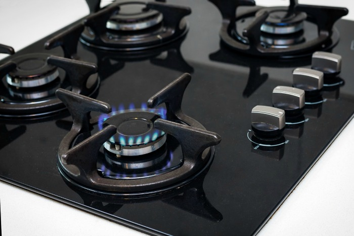 Gas stove with a burner lit.