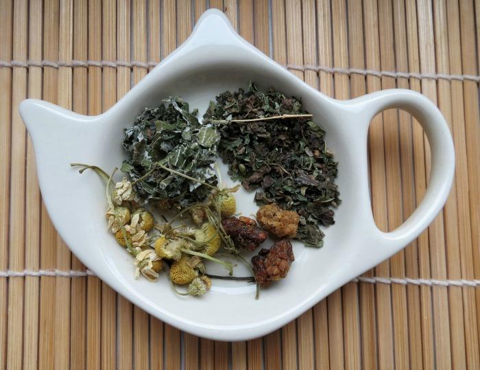 Fresh herbs in a tea pot shaped dish on a bamboo mat.