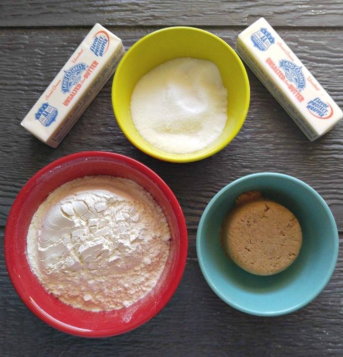 Butter, sugar, brown sugar, flour on a wooden board.