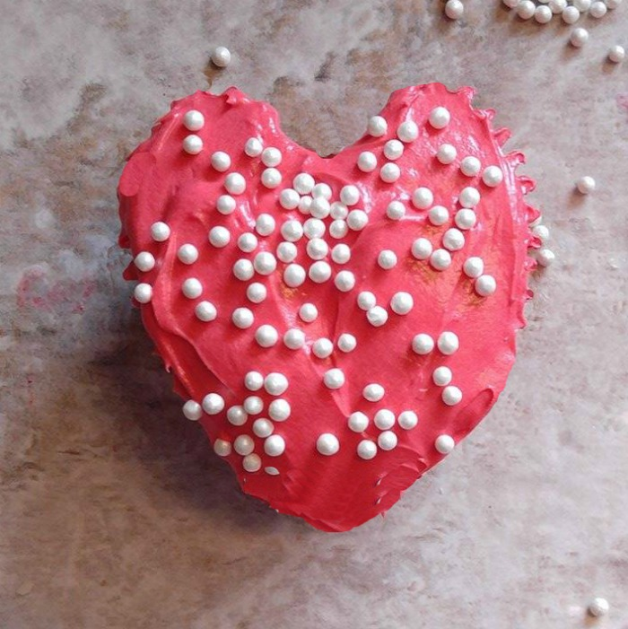 Heart cupcake with red frosting and candy pearls