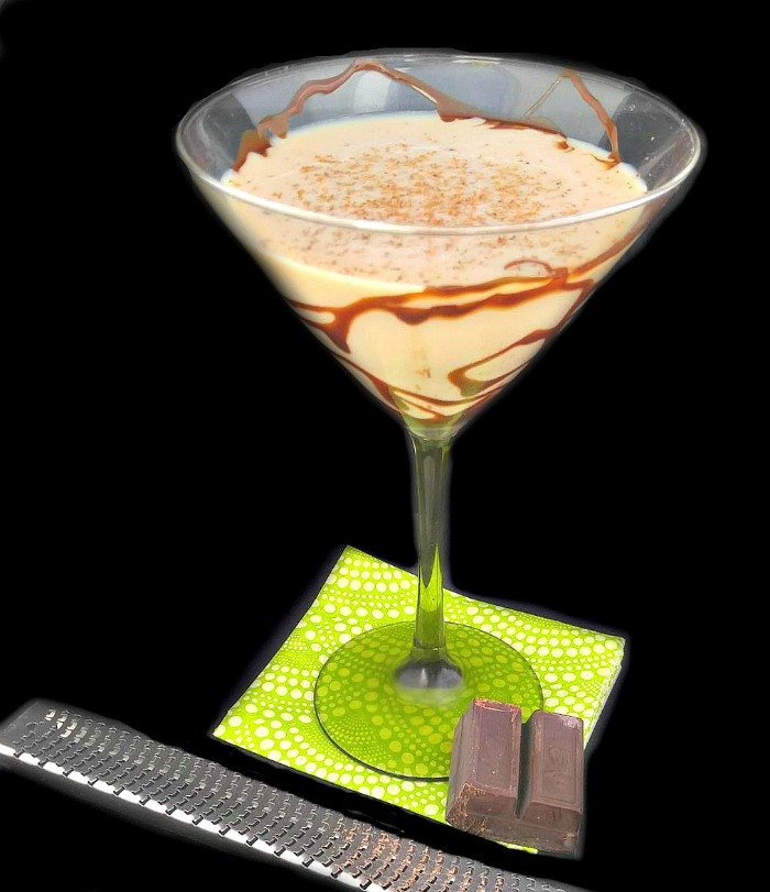 Creamy Frangelico cocktail in a drizzled martini glass with grated chocolate on a green napkin.