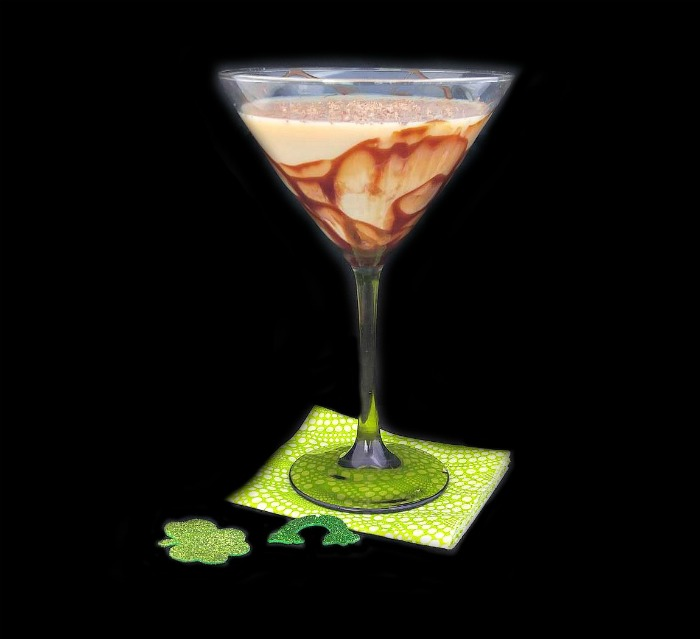 Bailey's martini with a chocolate drizzled glass on a green napkin with shamrock and rainbow pieces.