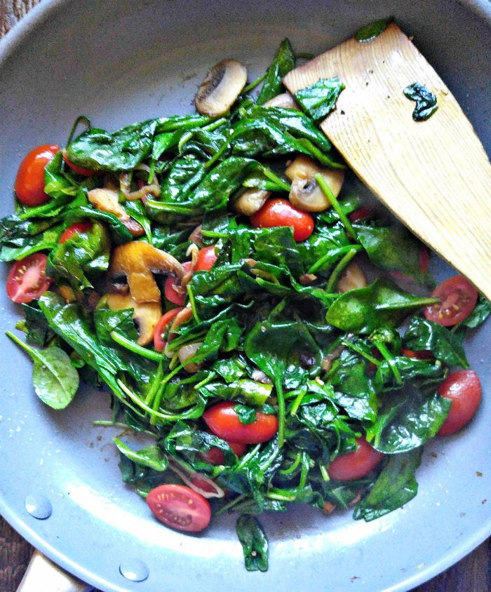 Add spinach and grape tomatoes to the mushrooms