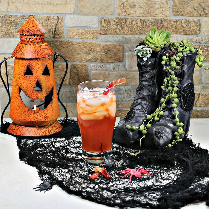 Witches brew drink with witch shoes and pumpkin.