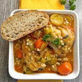 Bowl of one pot chicken barley stew with crusty bread