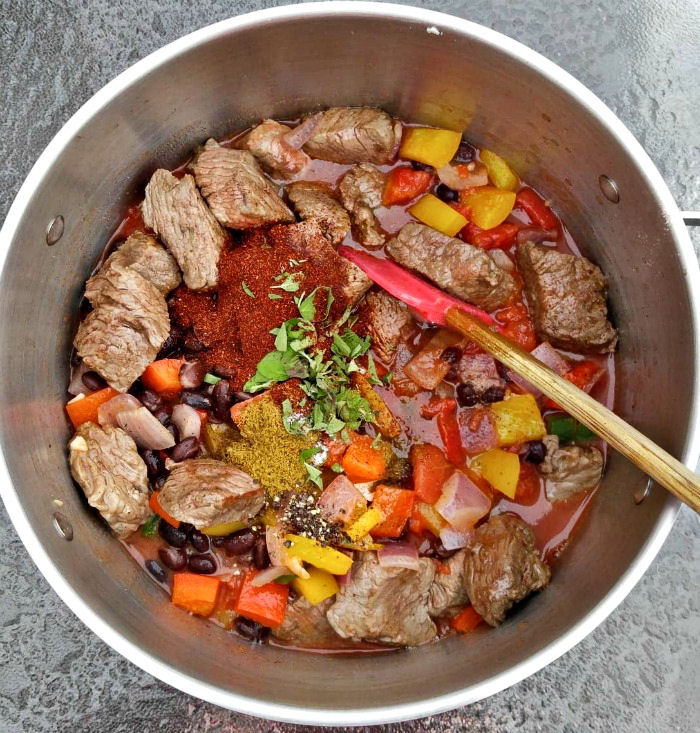 Add cooked beef and herbs to the chili pot