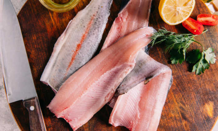 Rainbow trout fillets on a cutting board with lemon and herbs and a knife.