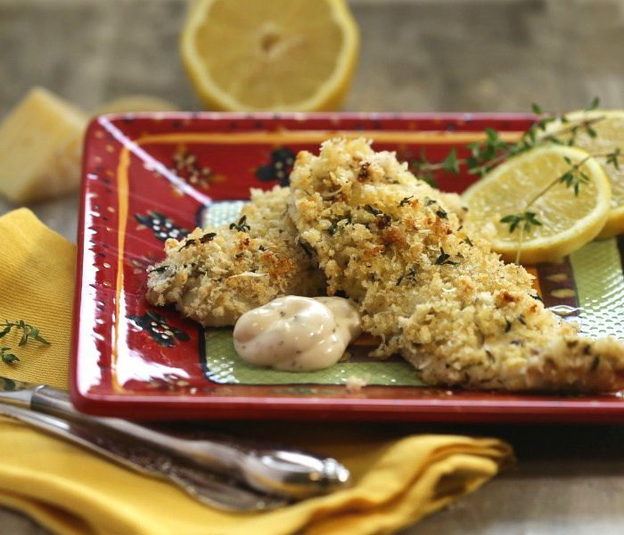 Baked trout recipe with tartar sauce on a red plate with lemons and thyme.
