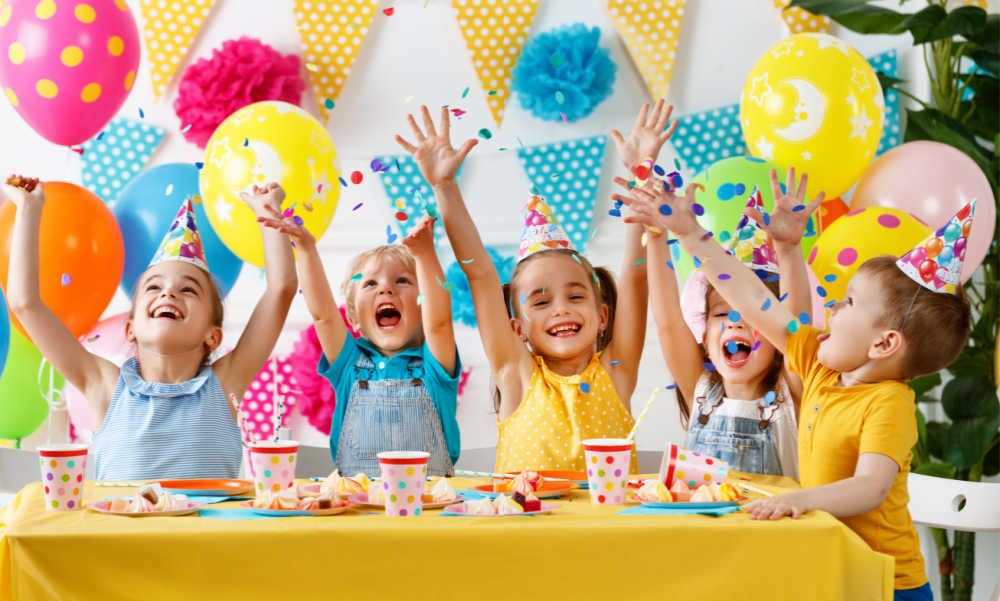 Kids with arms raised and balloons and party food.
