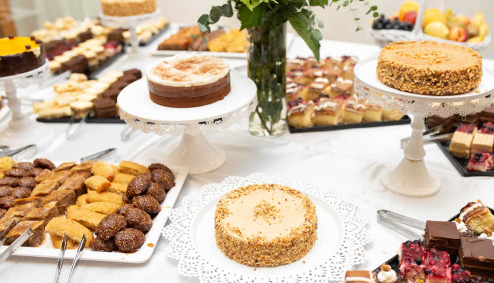 Cakes and other desserts on levels on a party table.