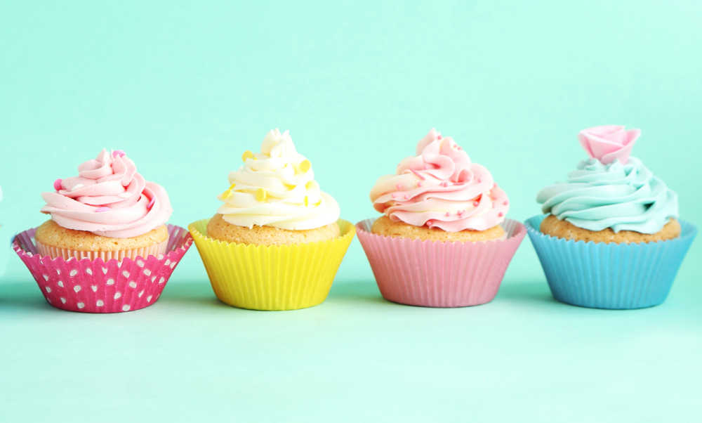 Decorated pastel cupcakes in fancy liners.