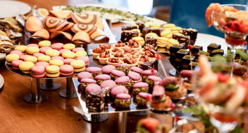 Cupcakes, and other sweet treats set up on a dessert table.