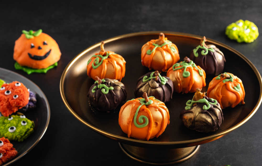 Pumpkin cake pops and ,monster cookies on a sweets table for Halloween.
