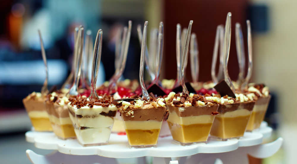 Individual sized portions with serving spoons inserted into dessert.