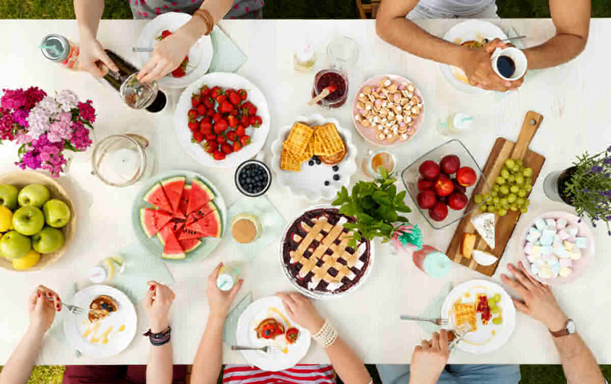 Summer party with hands on a dessert table.