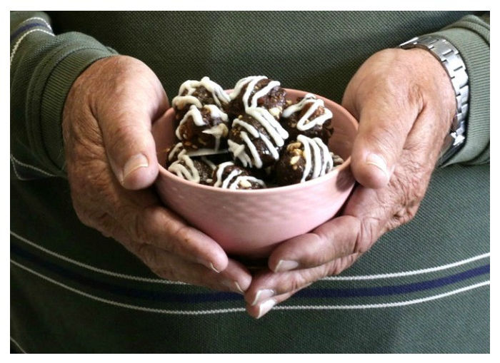 Man holding a bowl of almond butter energy bites.